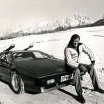Roger Moore sits on his Lotus Esprit Turbo
